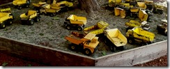 sandbox-of-yellow-toy-trucks